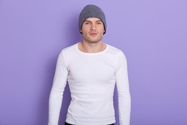 Nahaufnahmeporträt des hübschen magnetischen mannes, der isoliert auf flieder in steht, grauen hut und weißes sweatshirt tragend, starke passform hält. konzept der kalten zeiten.