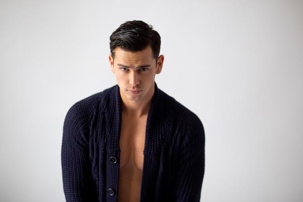 Nahaufnahmeporträt des hübschen passenden brünetten jungen mannes im schwarzen pullover
