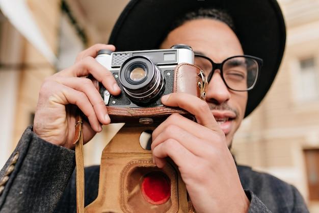 Nahaufnahmeporträt des hübschen schwarzen mannes in den eleganten gläsern, die fotos mit kamera machen. konzentrierter afrikanischer fotograf, der im freien arbeitet.