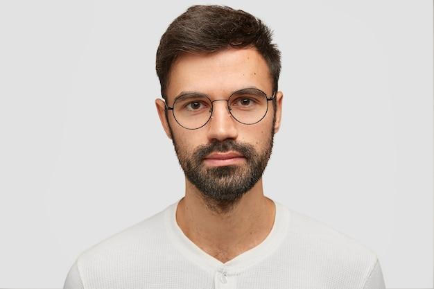 Nahaufnahmeporträt des hübschen unrasierten mannes mit dickem bart und schnurrbart, hat dunkles haar, sieht ernst aus