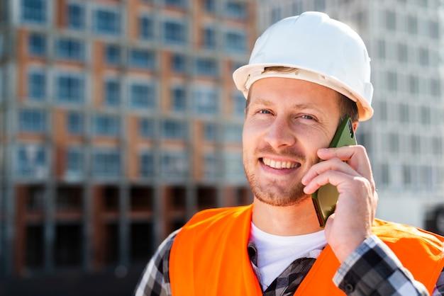 Nahaufnahmeporträt des ingenieurs sprechend am telefon