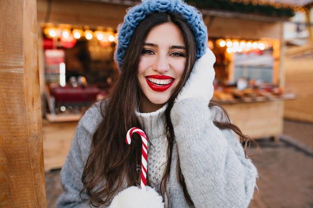 Nahaufnahmeporträt des inspirierten mädchens in den warmen weißen handschuhen, die mit weihnachtszuckerstange aufwerfen.