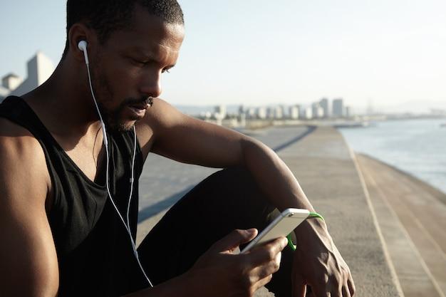 Nahaufnahmeporträt des jungen bärtigen mannes, der musik hört