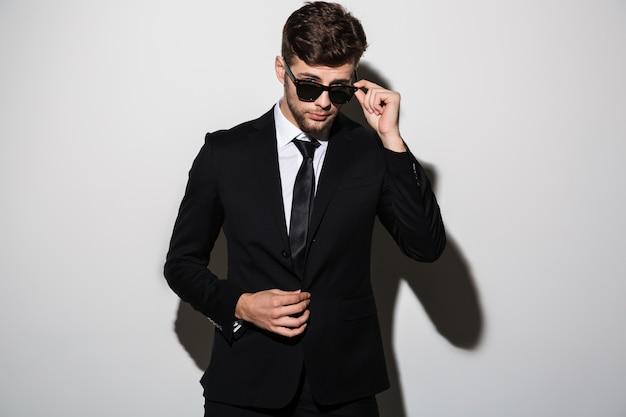 Nahaufnahmeporträt des jungen bärtigen mannes im schwarzen anzug, der seine sonnenlasse berührt