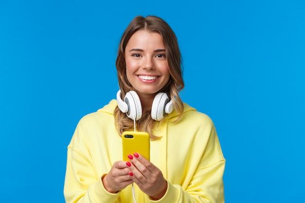 Nahaufnahmeporträt des jungen blonden europäischen hipster-mädchens mit blondem kurzen haar und kopfhörern über hals, haltendes smartphone, sms, handy, blaue wand