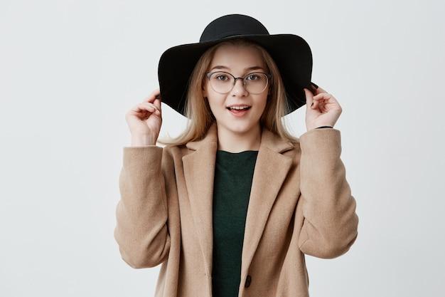 Nahaufnahmeporträt des jungen blonden mädchens mit reiner haut, brille und lächeln, die schwarzen hut und mantel lokalisiert tragen. hübsche frau, die ihren stil genießt.
