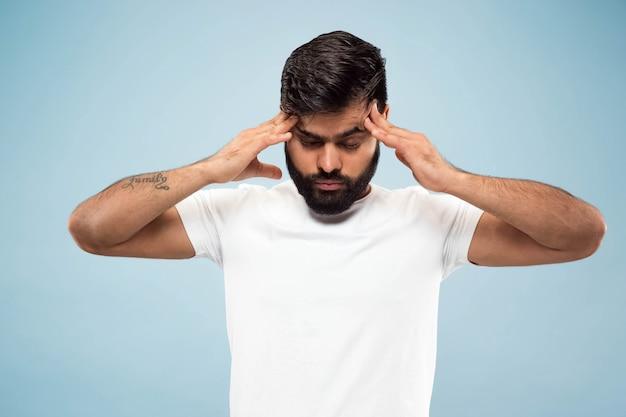 Nahaufnahmeporträt des jungen indischen mannes im weißen hemd. konzentration, kopfschmerzen.