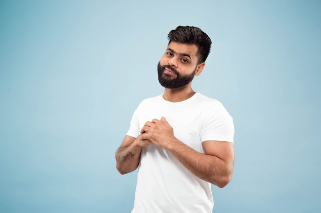 Nahaufnahmeporträt des jungen indischen mannes im weißen hemd. posieren, stehen und lächeln sieht ruhig aus.