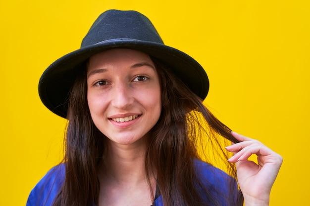Nahaufnahmeporträt des jungen kaukasischen mädchens im schwarzen hut und in der blauen jacke