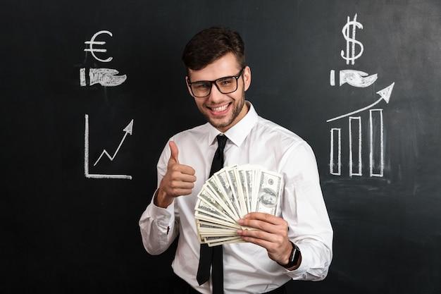 Nahaufnahmeporträt des jungen lächelnden geschäftsmannes, der bündel geld hält, während daumen hoch geste zeigt