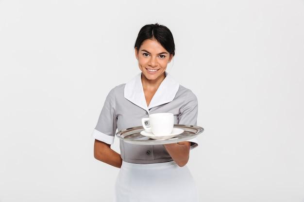 Nahaufnahmeporträt des jungen lächelnden weiblichen kellners in der uniform, die metallschale mit tasse kaffee hält