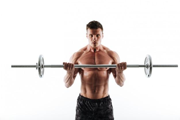 Nahaufnahmeporträt des jungen mächtigen bodybuilders, der mit langhantel trainiert
