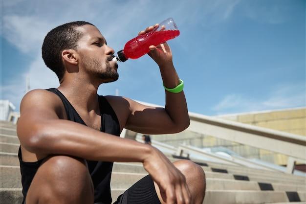 Nahaufnahmeporträt des jungen mannes, der sich hydratisiert