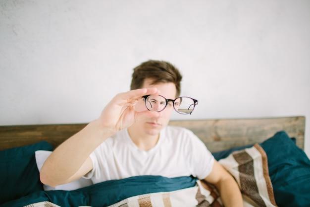 Nahaufnahmeporträt des jungen mannes mit brille. er hat sehprobleme und kniff die augen ein wenig zusammen. der hübsche mann hält seine brille mit einer hand direkt vor die kamera