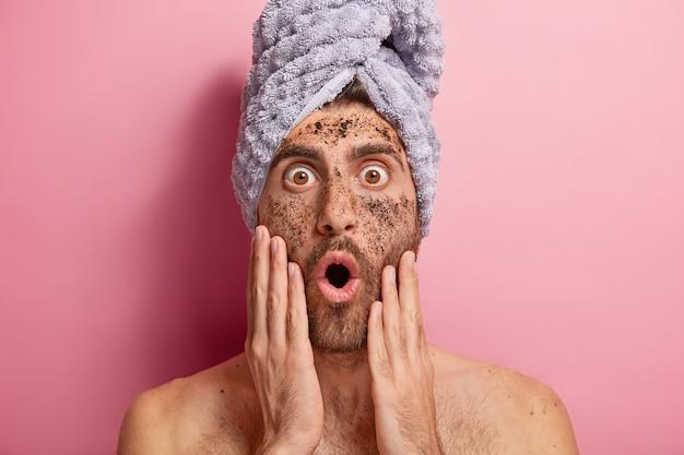 Nahaufnahmeporträt des jungen mannes reinigt gesicht mit peeling, starrt mit abgehörten augen und geöffnetem mund, vergisst kosmetische creme, trägt handtuch, hat nackten körper