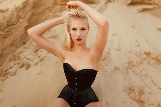 Nahaufnahmeporträt des jungen modells mit blondem haar und make-up, im schwarzen sexy bodysuit, seine hände über seinem kopf haltend, auf dem sandboden in der wüste sitzend.