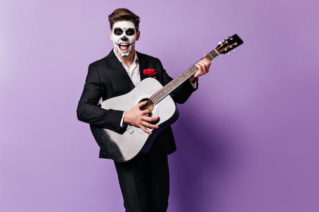 Nahaufnahmeporträt des kerls, der serenade im halloween-kostüm singt. mann mit rose in seiner tasche, die auf lokalisiertem hintergrund aufwirft.