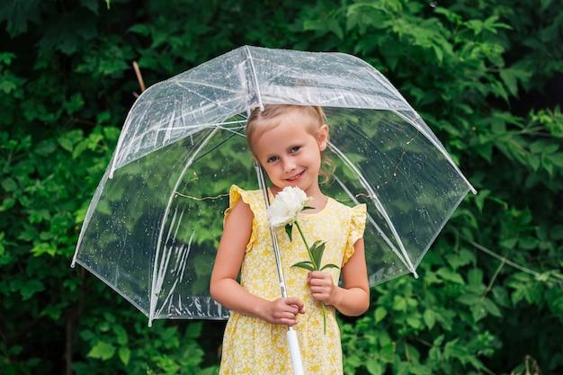 Nahaufnahmeporträt des kleinen kaukasischen mädchens mit transparentem regenschirm in gelbem kleid und regenstiefeln im parksommer