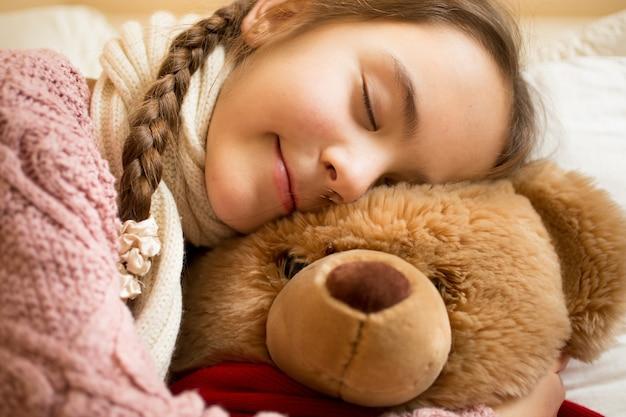 Nahaufnahmeporträt des kleinen mädchens, das auf braunem teddybären schläft