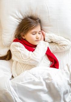 Nahaufnahmeporträt des kleinen mädchens im pullover, das im bett schläft