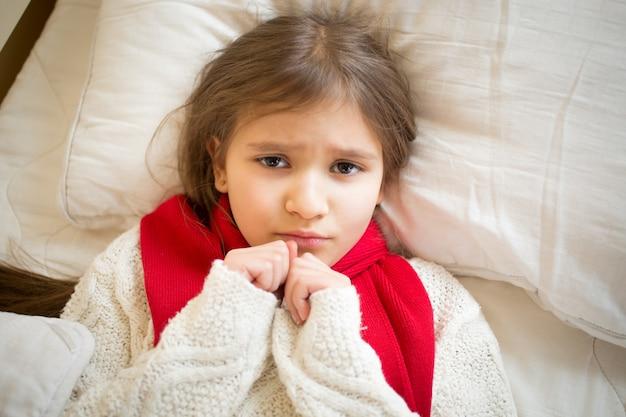 Nahaufnahmeporträt des kleinen traurigen mädchens mit der grippe, die im bett liegt