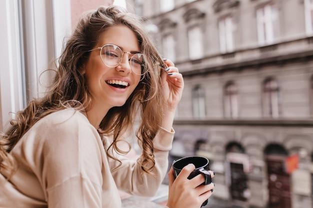 Nahaufnahmeporträt des lachenden brünetten mädchens im beigen pullover, der kaffee auf stadthintergrund trinkt