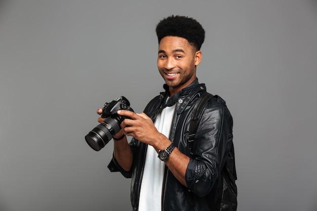 Nahaufnahmeporträt des lächelnden afrikanischen fotografen, der fotokamera hält