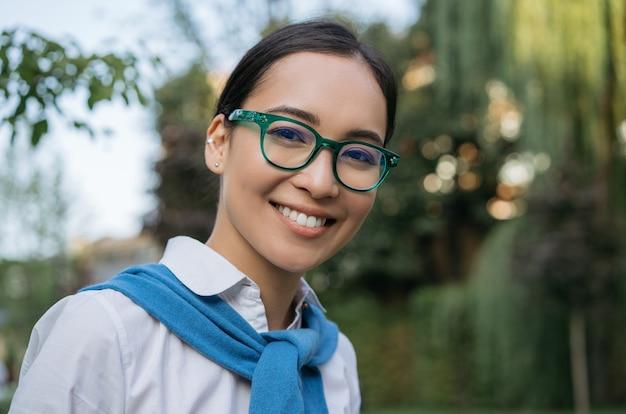 Nahaufnahmeporträt des lächelnden asiatischen studenten tragenden brillen, die kamera im freien, bildungskonzept betrachten