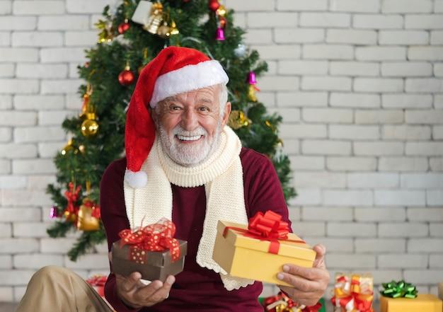 Nahaufnahmeporträt des lächelnden hübschen kaukasischen älteren mannes im roten pullover, im schal und im sankt-hut, der weihnachtsgeschenke vor verziertem weihnachtsbaum hält. schönen winterurlaub.