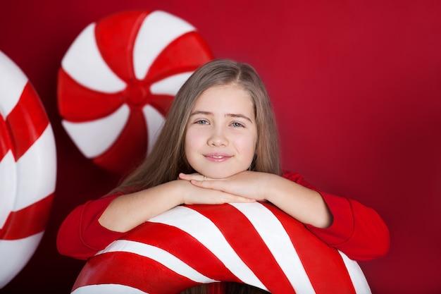 Nahaufnahmeporträt des lächelnden kleinen mädchens mit großen weihnachtsbonbons auf rotem hintergrund.