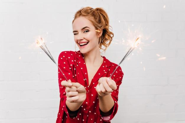 Nahaufnahmeporträt des lächelnden liebenswerten mädchens, das neues jahr mit wunderkerzen feiert. anmutige frau im lustigen roten pyjama, der auf weihnachten wartet.