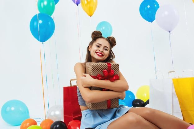 Nahaufnahmeporträt des lächelnden mädchens, das große geschenkbox umarmt