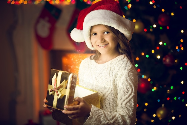 Nahaufnahmeporträt des lächelnden mädchens in der weihnachtsmütze, das mit glühender geschenkbox aufwirft