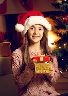 Nahaufnahmeporträt des lächelnden mädchens in der weihnachtsmütze mit roter geschenkbox