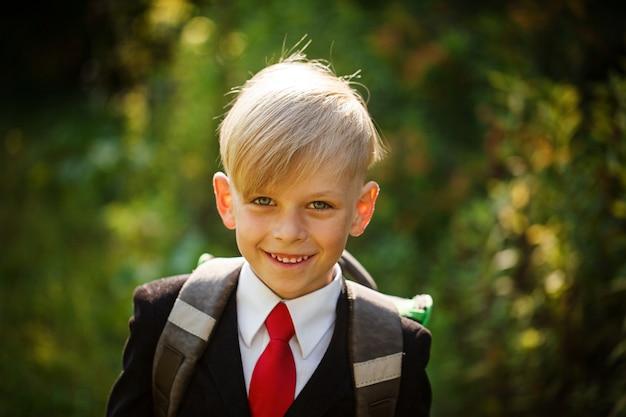 Nahaufnahmeporträt des lächelnden schülers netter junge, der zurück zur schule geht. kind mit rucksack am ersten schultag.