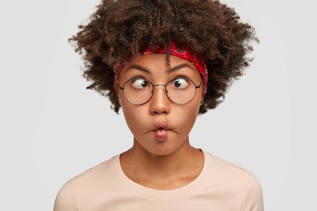 Nahaufnahmeporträt des lustigen afroamerikanischen mädchens macht grimasse, kreuzt augen geldbörsen lippen