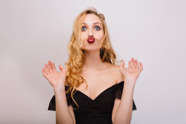 Nahaufnahmeporträt des lustigen blonden mädchens, das verrückt ist, spaß hat, gesichter macht, schnurrbart mit haaren imitiert. sie hat schöne lockige haare, rote lippen. schwarzes kleid tragen. isoliert..