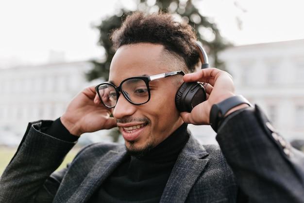 Nahaufnahmeporträt des lustigen überraschten kerls, der musik auf der straße hört. afrikanischer mann in den gläsern, die in den kopfhörern aufwerfen
