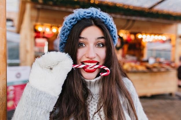 Nahaufnahmeporträt des lustigen weiblichen modells mit dunklem haar, das mit vergnügen zuckerstange in weihnachten isst. frohes brünettes mädchen in den weißen handschuhen, die lollipop am kalten tag genießen.