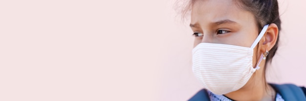 Nahaufnahmeporträt des mädchens mit schützender medizinischer gesichtsmaske gegen coronavirus
