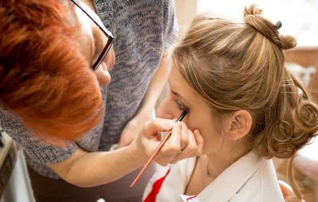 Nahaufnahmeporträt des maskenbildners, der braut-make-up anwendet