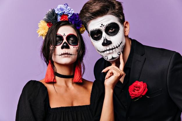 Nahaufnahmeporträt des mexikanischen kerls und des mädchens mit gesichtskunst. paar in ungewöhnlichen kleidern, die arrogant in die kamera schauen.