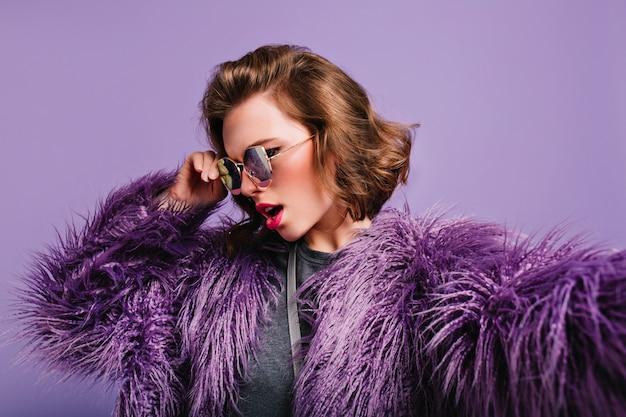 Nahaufnahmeporträt des modischen weiblichen modells mit der kurzen lockigen frisur, die in der sonnenbrille aufwirft