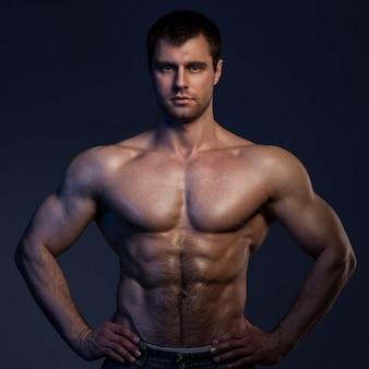 Nahaufnahmeporträt des muskulösen kerls in der dunkelheit
