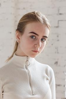 Nahaufnahmeporträt des nachdenklichen jugendlich modells mit blauen augen, die weißen pullover tragen