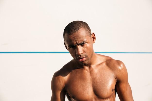 Nahaufnahmeporträt des nassen afroamerikanischen sportmannes, der nach dem training ruht