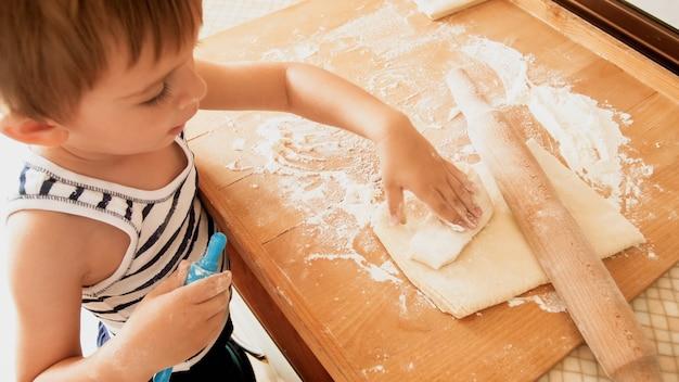 Nahaufnahmeporträt des netten 3 jahre kleinkindjungen, der auf küche steht und teig kocht. kind backen und frühstücken