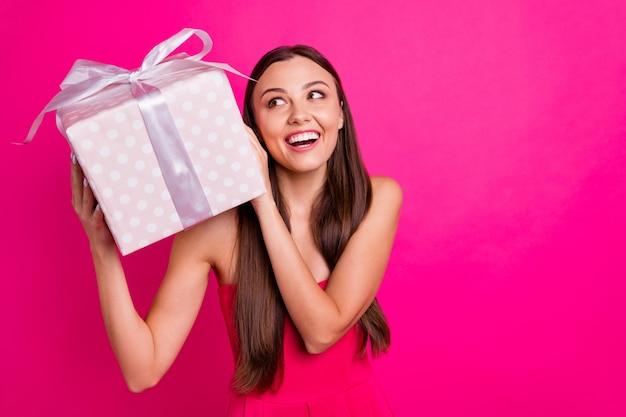 Nahaufnahmeporträt des netten attraktiven herrlichen fröhlichen neugierigen langhaarigen mädchens, das in den händen festliche schachtel hält, die errät, was innen auf hellem lebendigem glanz lebhaftem rosa fuchsiafarbhintergrund lokalisiert wird