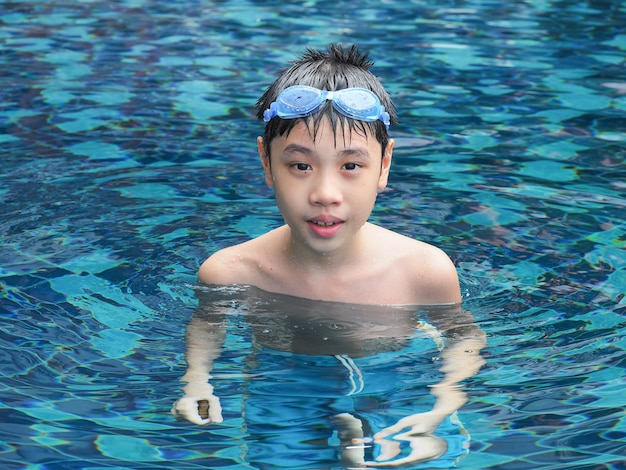Nahaufnahmeporträt des netten jungen im swimmingpool