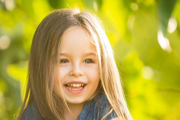 Nahaufnahmeporträt des netten kleinen mädchens. sommerfrühlingskind. nettes hübsches auf unschärfehintergrund im freien.